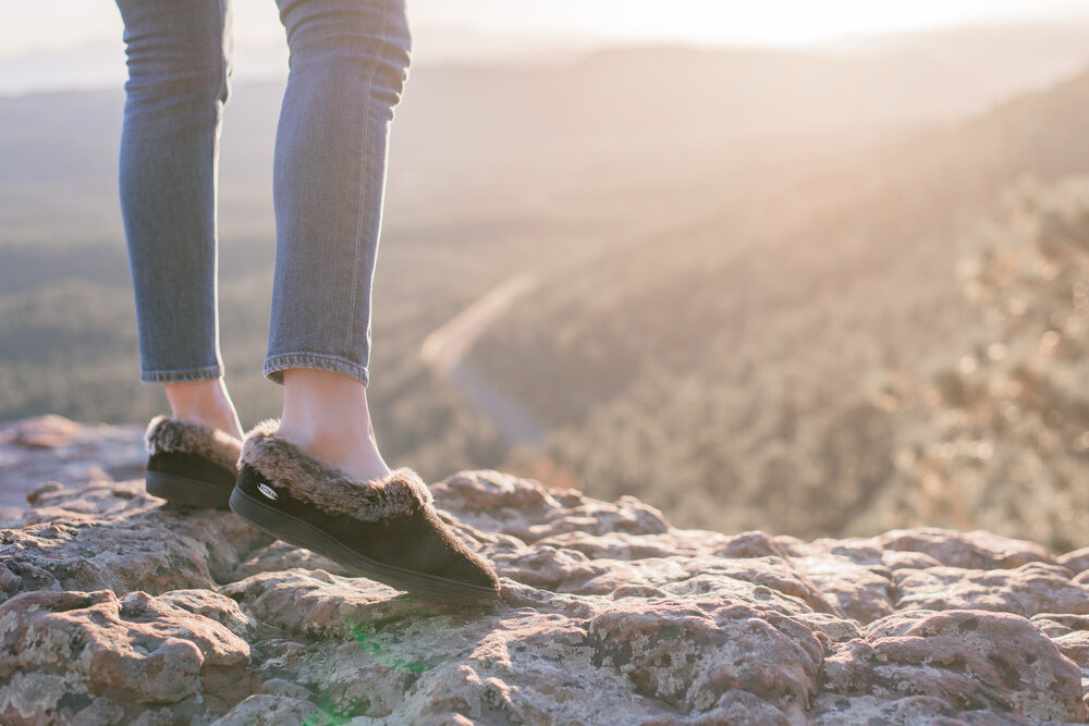 20 fun fall bucket list ideas for families by top US lifestyle blog, Love + Specs: image of a woman watching the sunset in Arizona wearing Acorn slippers