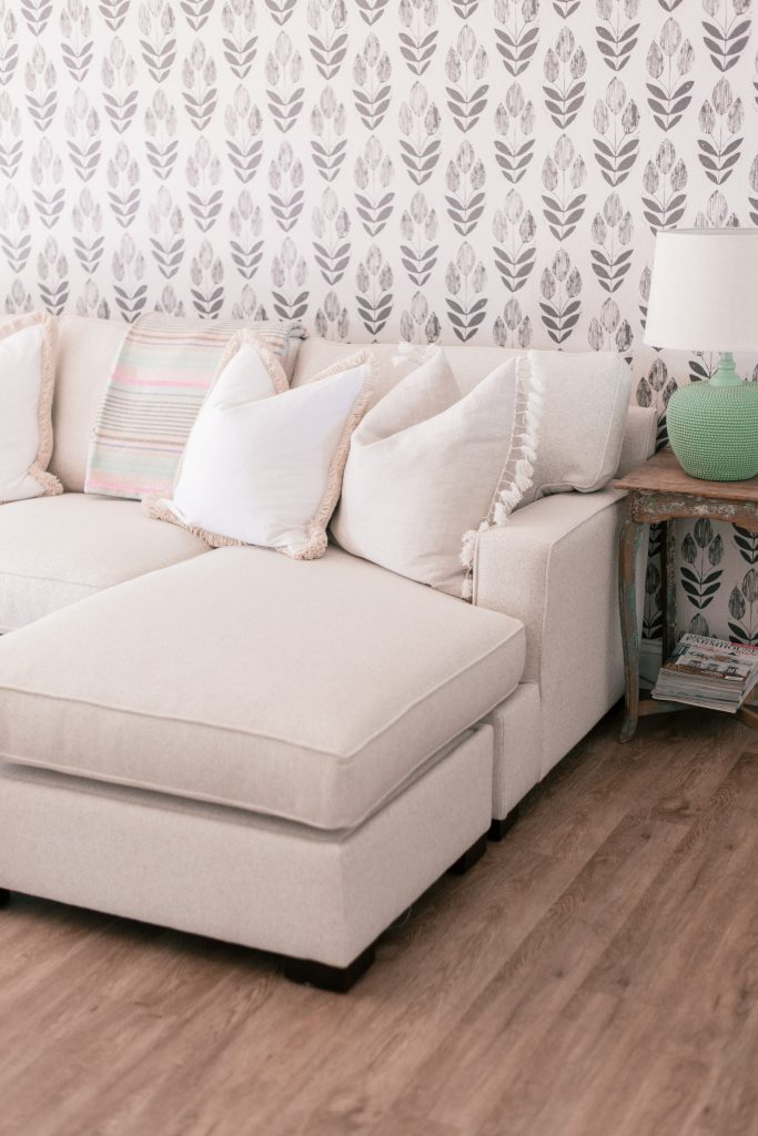 Cottage Style by popular Phoenix life and style blog, Love and Specs: image of a cream colored sectional couch with white throw pillows next to a distressed end table with a milk glass lamp.