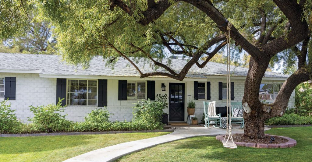 Best White Exterior Paint Colors by popular Phoenix life and style blog, Love and Specs: image of a white brick house with black shutters.