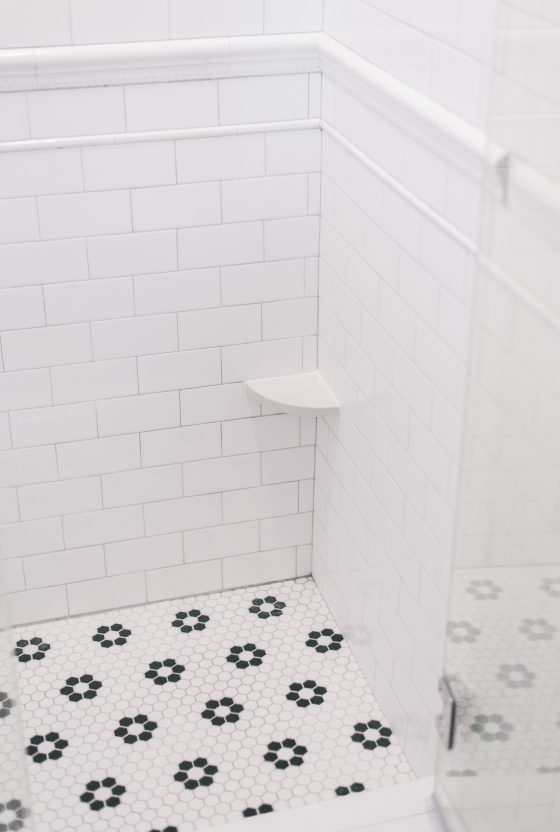 Corner Shower Foot Rest by popular Phoenix life and style blog, Love and Specs: image of a white marble corner shower foot rest in a corner shower with white subway tile and black and white hexagon tiles.