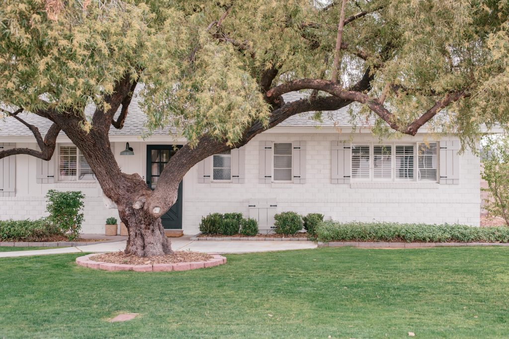 Best White Exterior Paint Colors by popular Phoenix life and style blog, Love and Specs: image of a white brick house with grey shutters.