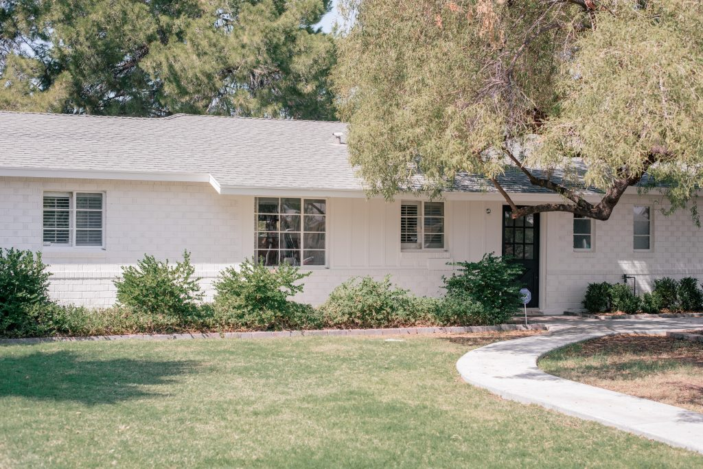Best White Exterior Paint Colors by popular Phoenix life and style blog, Love and Specs: image of a white brick house.
