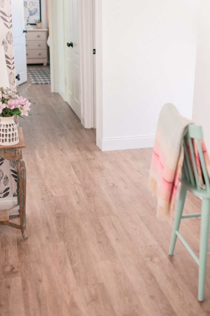 Vinyl Plank Flooring by popular Phoenix life and style blog, Love and Specs: image of vinyl plank flooring and a mint green chair with a pastel pink stripe blanket draped over it.